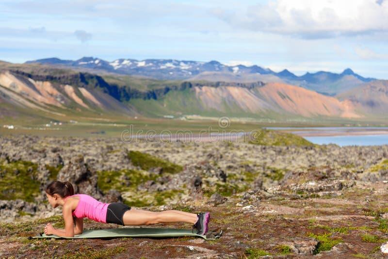 Öva konditionkvinnan som gör plankan i natur arkivfoton