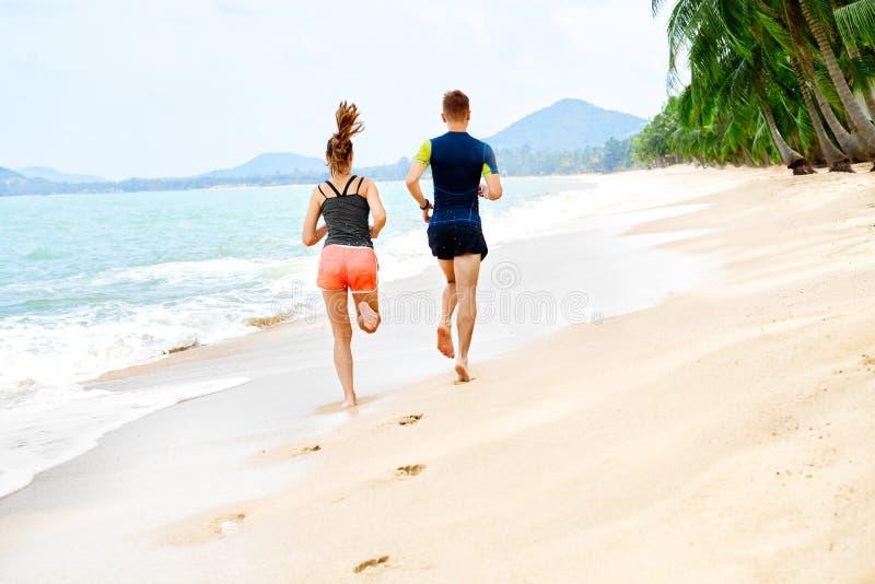 öva lycklig running för strandpar Sportar kondition läka arkivfoton