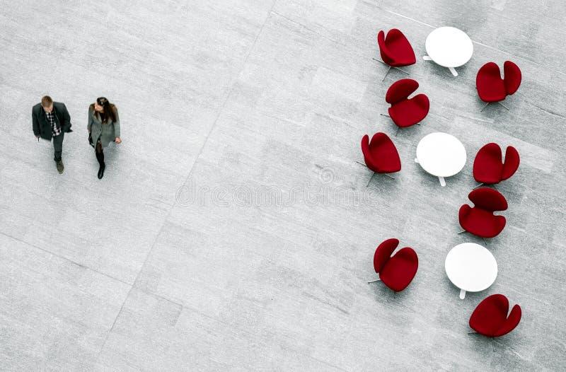 Öva påtryckningar väntande område med fåtöljer, tabeller och par av folk arkivbild