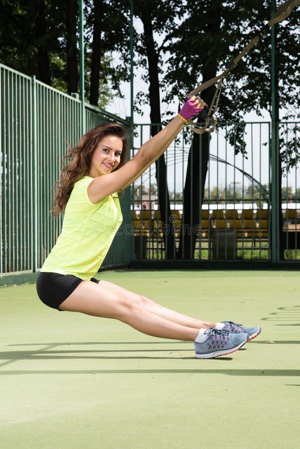 Öva utomhus i solig dag Övningar med TRX Härlig ung kvinna i idrotts- form royaltyfri bild