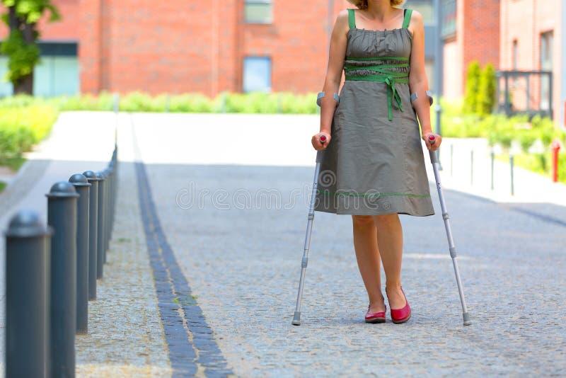 Övande gå för kvinna på kryckor arkivfoto