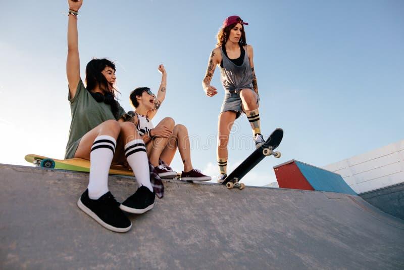 Övande skateboarding för flicka med att hurra för vänner royaltyfri bild