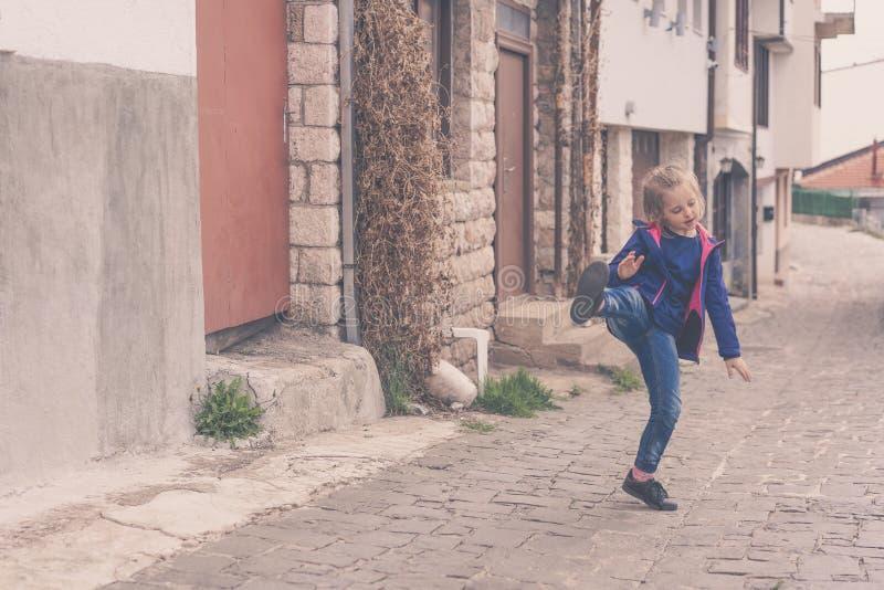 Övande sparkar för liten flicka på en gata arkivfoton