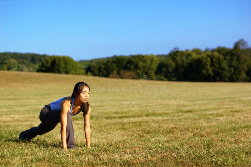 övande yoga för fältflicka arkivbild