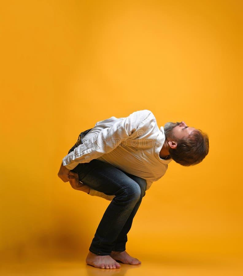 Övande yoga för gamal man som gör sträcka övningar mot gul bakgrund arkivfoton
