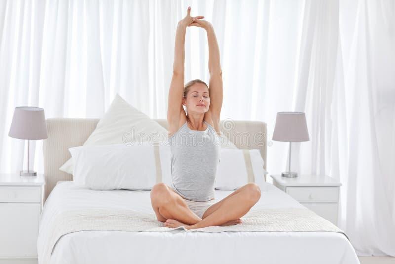 Övande yoga för härlig kvinna på henne underlag arkivbilder