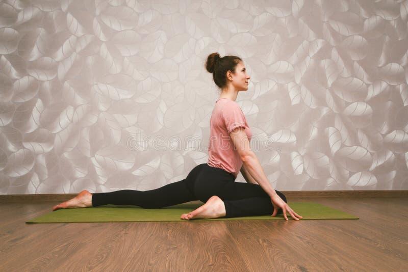 Övande yoga för kvinna, hem- genomkörarebegrepp royaltyfri fotografi