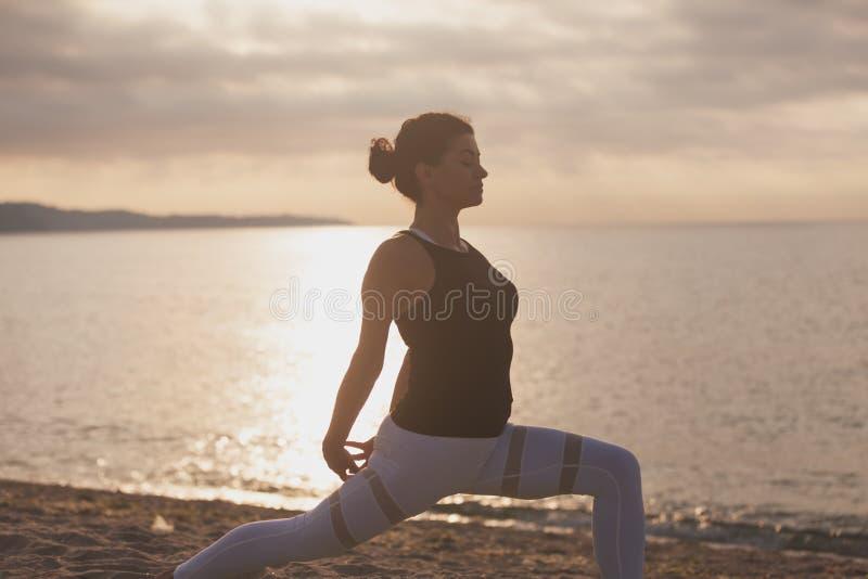 Övande yoga för kvinna på stranden på soluppgång Utomhus sportar sund living arkivbild
