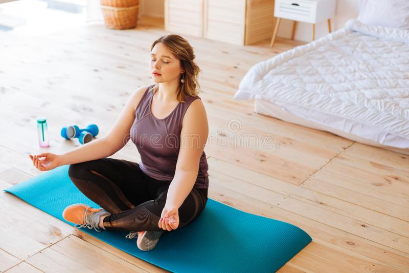 ?vande yoga f?r trevlig attraktiv kvinna hemma royaltyfri fotografi