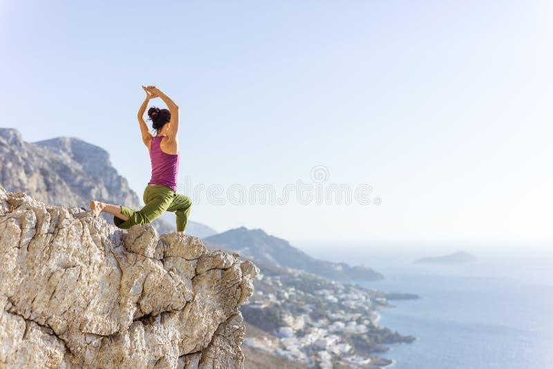 Övande yoga för ung Caucasian kvinna eller utarbeta, medan stå på klippan royaltyfri foto