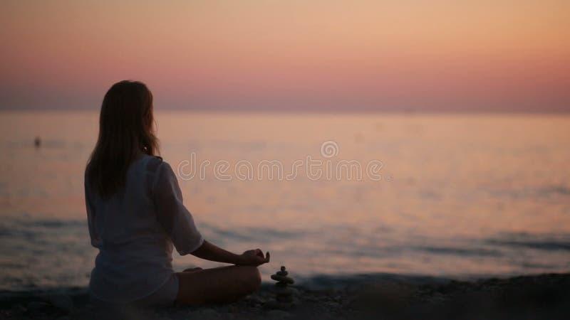 Övande yoga för ung kvinna på stranden på solnedgången lugnat hav
