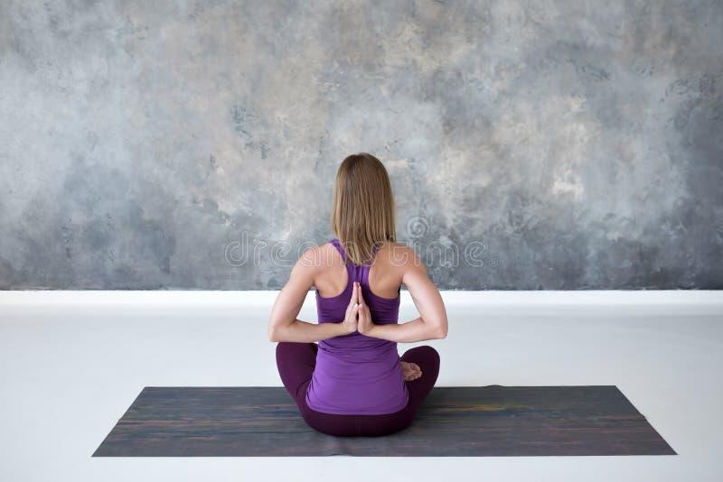 Övande yoga för ung kvinna som sitter med Namaste bak hennes baksida som utarbetar royaltyfri foto