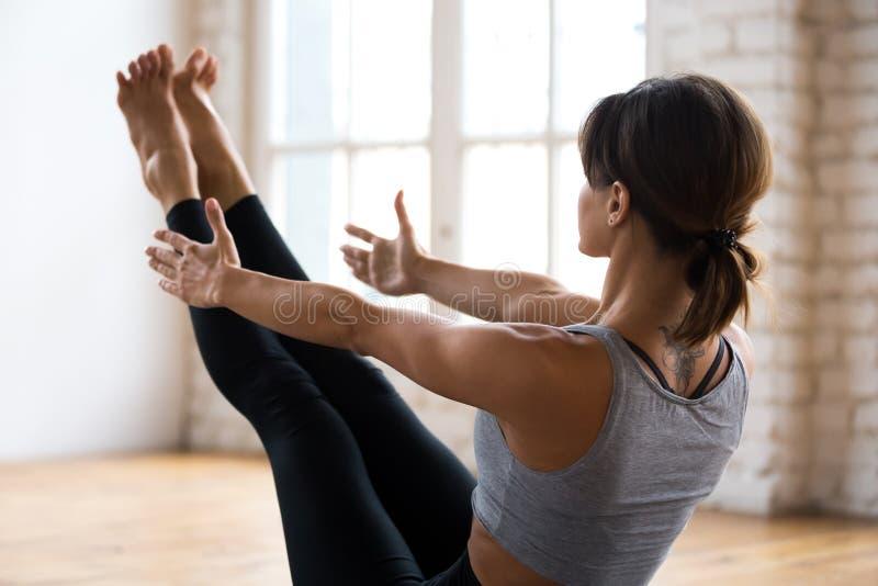 Övande yoga för ung sportig attraktiv kvinna, Paripurna Navasan royaltyfria foton