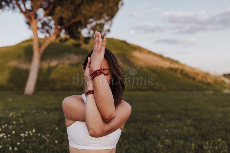Övande yogamindfullness för ung härlig asiatisk kvinna på solnedgången utomhus Sportar och sund livsstil royaltyfri foto