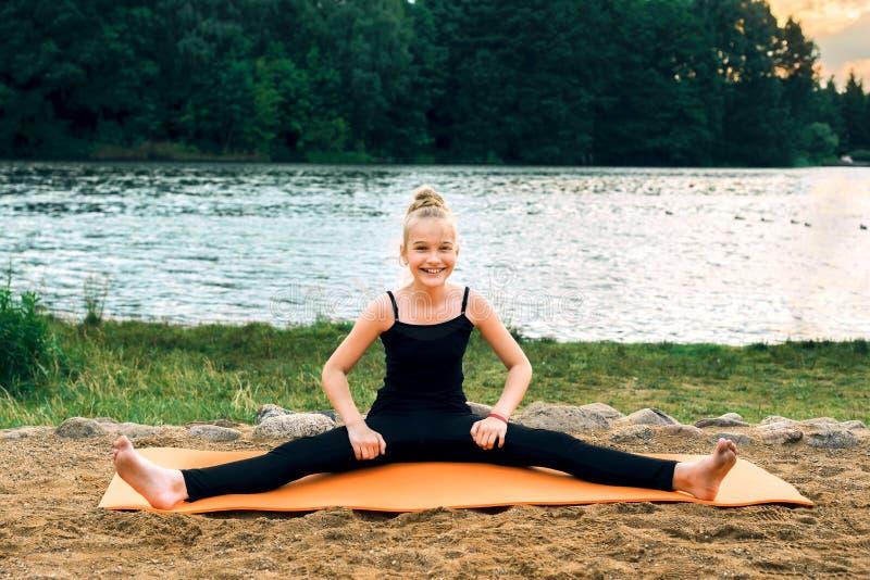 Övande yogapilates för lyckligt barn på flodbanken royaltyfria foton