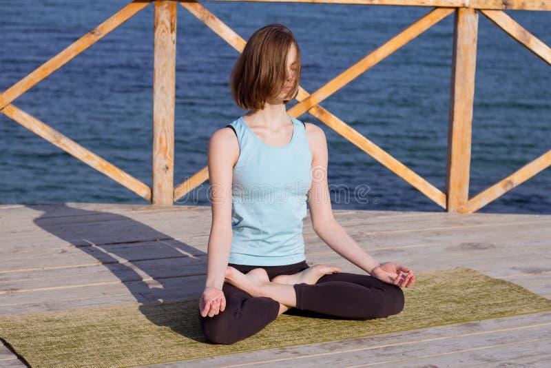 övar den färdiga kvinnan för nätt barn som gör yoga, på sommarstranden fotografering för bildbyråer