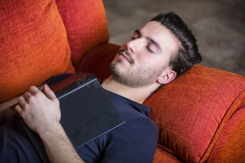 Över-arbetad trött ung man som sover med boken royaltyfri foto