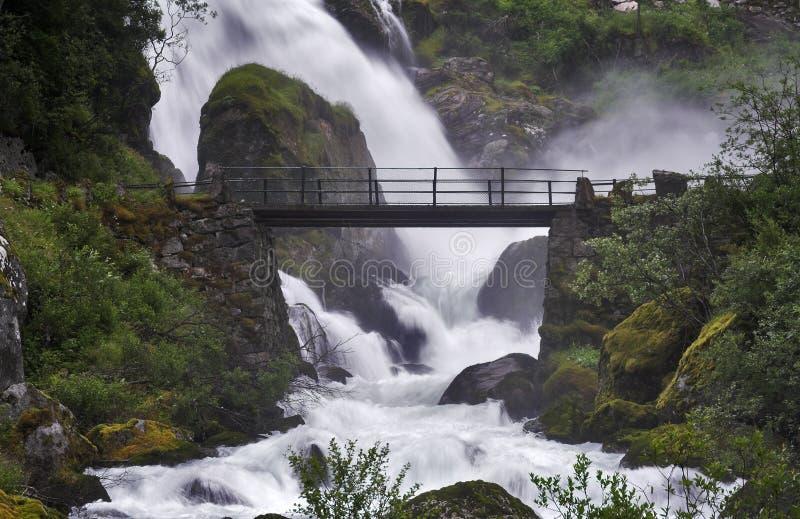 över bron nära den kraftiga strömvattenfallet royaltyfri bild