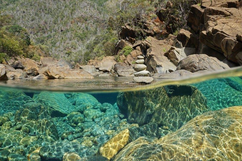 Över den undervattens- floden vaggar och bunten av kiselstenar royaltyfri foto