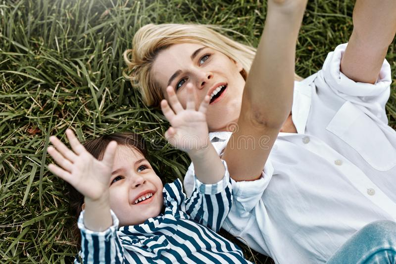 Över huvudet bild av den nätta blonda kvinnan som spelar med hennes gulliga lilla barn som ligger på utomhus- grönt gräs älska mo royaltyfri bild