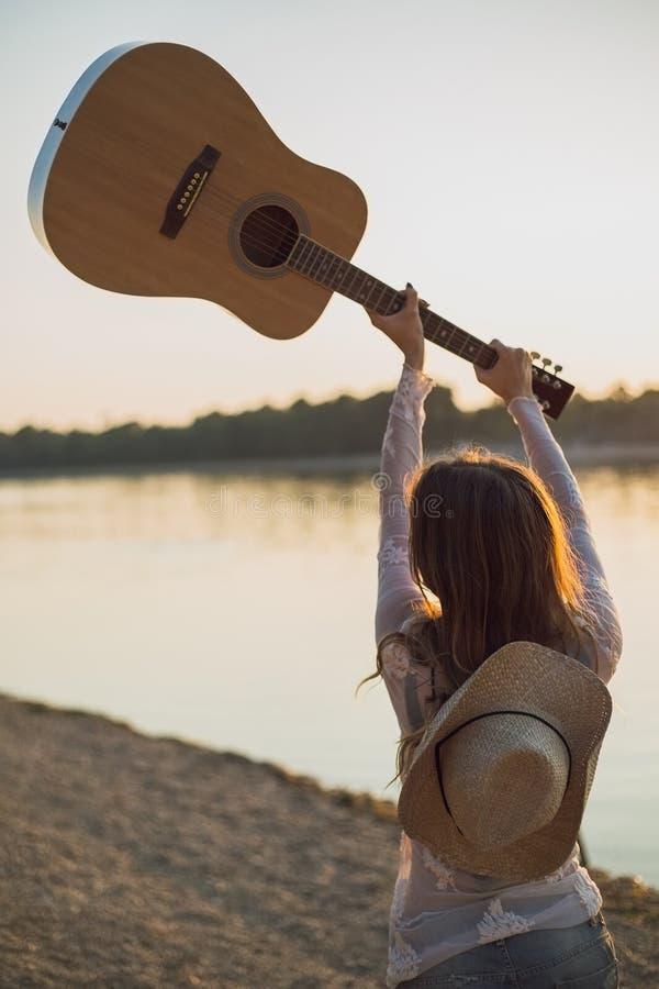 Över huvudet hållande gitarr för flicka arkivfoto