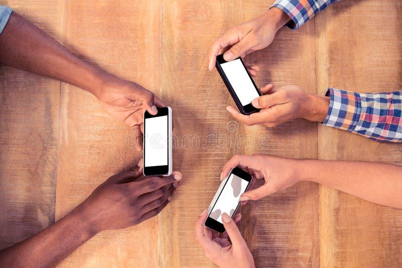 Över huvudet sikt av affärsfolk som använder smarta telefoner arkivbild