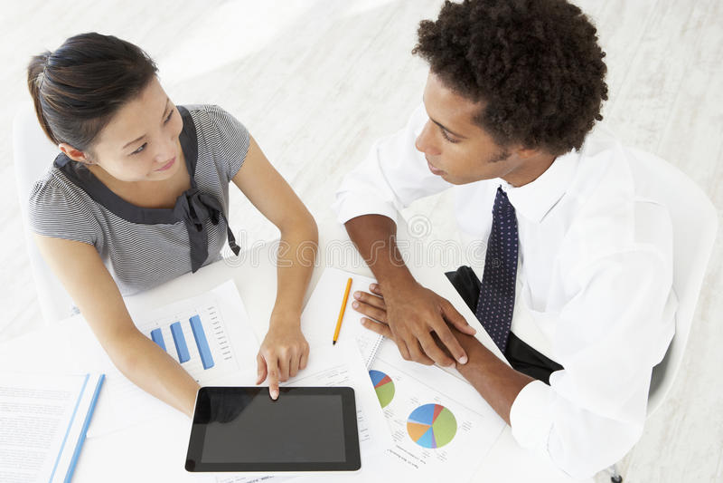 Över huvudet sikt av affärskvinnan And Businessman Working på skrivbordet som använder tillsammans den Digital minnestavlan arkivfoto