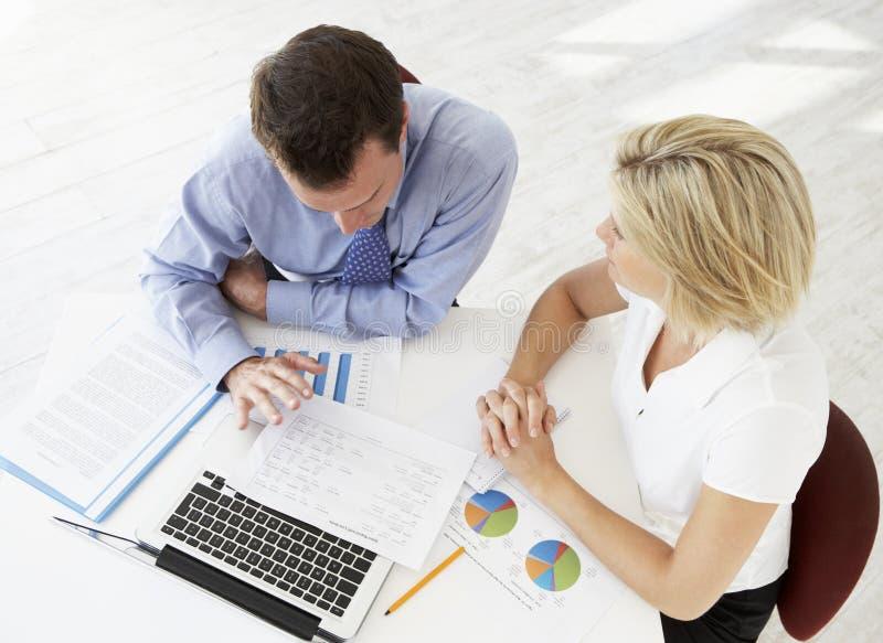 Över huvudet sikt av affärskvinnan And Businessman Working på skrivbordet tillsammans arkivfoto