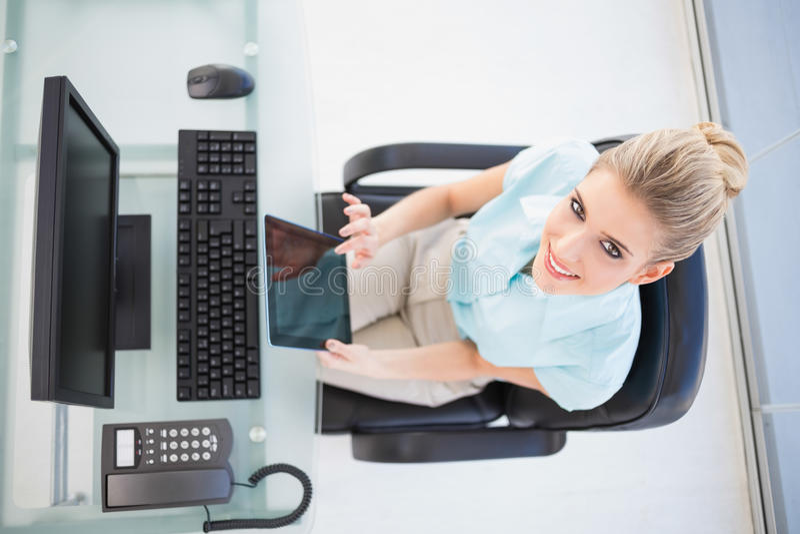 Över huvudet sikt av att le affärskvinnan som använder minnestavlan arkivbild