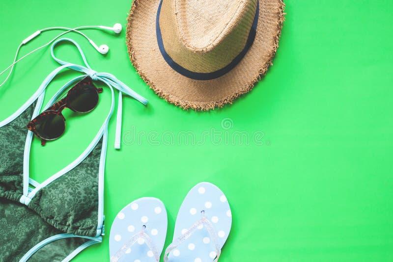 Över huvudet sikt av bikini- och flickatillbehör på bakgrund för grön färg, vårsommarmode royaltyfria foton