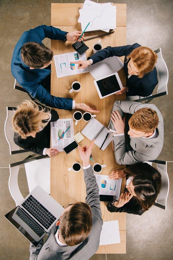över huvudet sikt av businesspeople på möte på tabellen med digitala apparatkaffekoppar royaltyfri foto