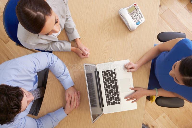 Över huvudet sikt av Businesspeople som i regeringsställning använder bärbara datorn arkivfoto