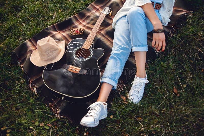 Över huvudet sikt av den härliga kvinnan med gitarren som vilar på grön gräsmatta Top beskådar arkivbild