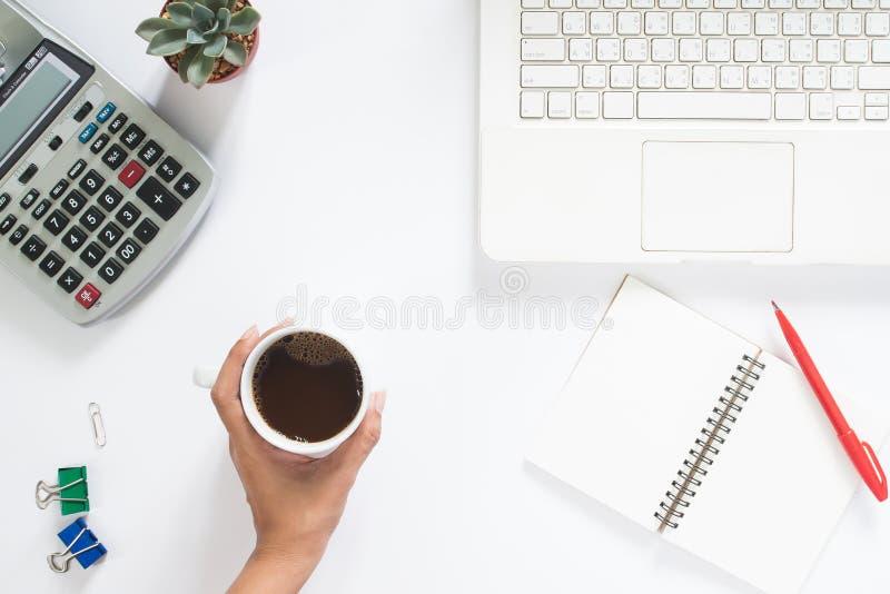 Över huvudet sikt av den hållande koppen kaffe för kvinnahand med bärbara datorn royaltyfria foton