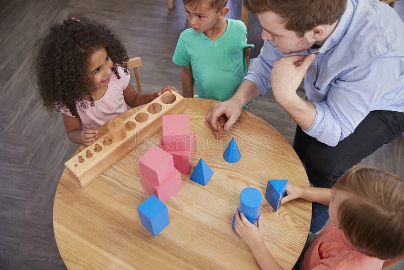 Över huvudet sikt av det lärareAnd Pupils At skrivbordet i den Montessori skolan royaltyfri foto