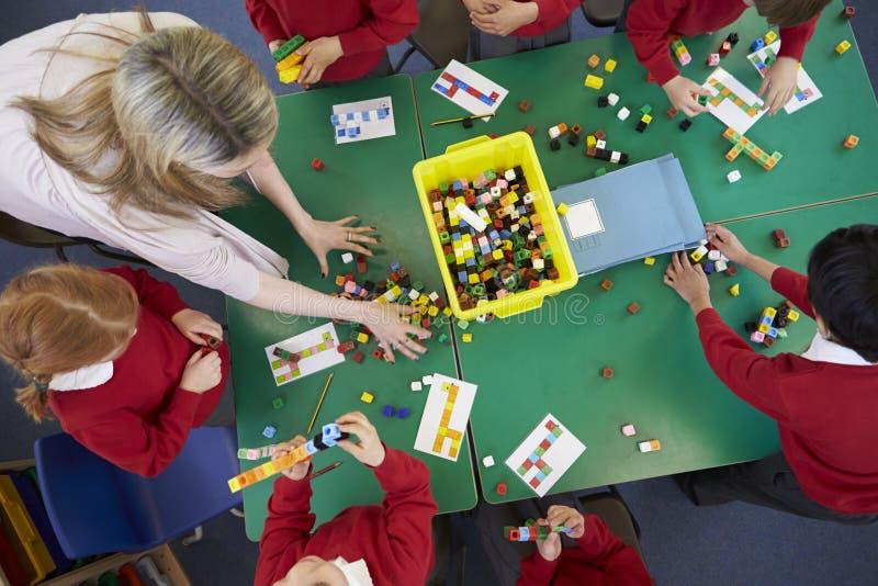 Över huvudet sikt av elever och läraren Working With Blocks fotografering för bildbyråer