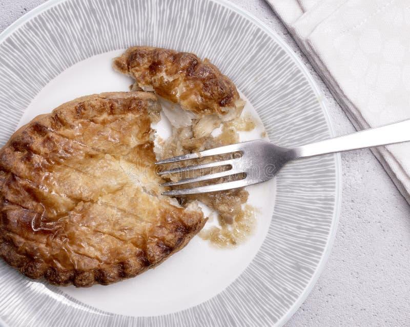 Över huvudet sikt av en feg paj på en platta med gaffeln royaltyfri fotografi
