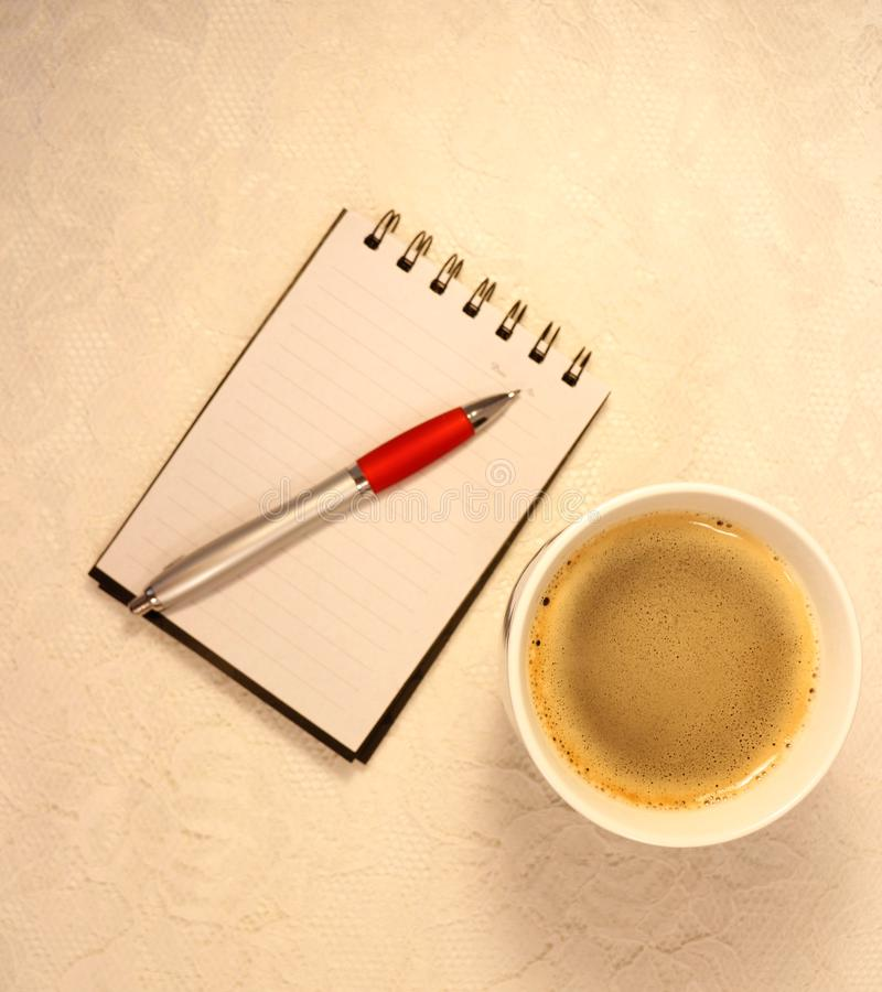 Över huvudet sikt av en kopp kaffe, anteckningsboken och en färgpulverblyertspenna arkivfoto