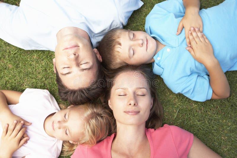 Över huvudet sikt av familjen som vilar på gräs royaltyfri bild
