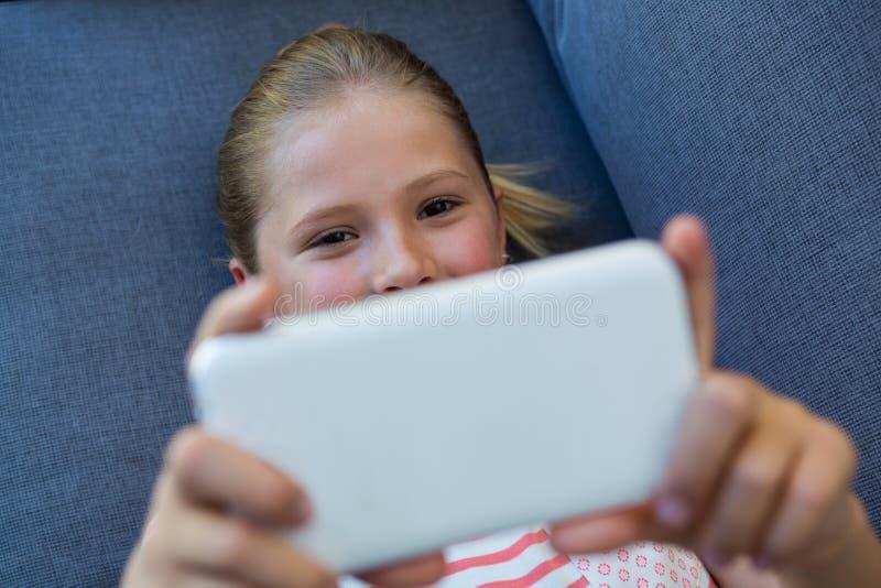 Över huvudet sikt av flickan som använder telefonen, medan ligga på soffan royaltyfri fotografi