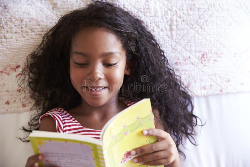 Över huvudet sikt av flickan som ligger på säng och läseboken royaltyfri foto
