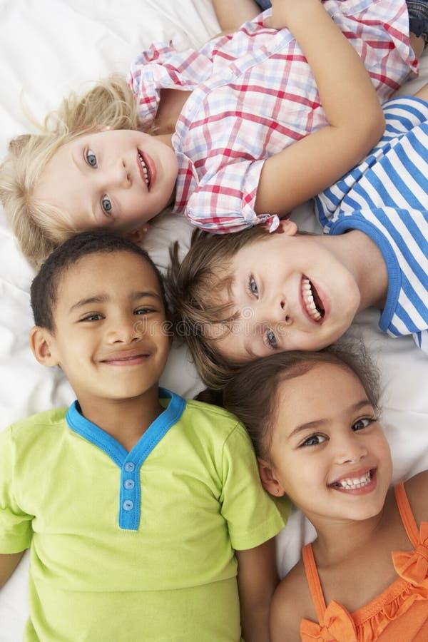 Över huvudet sikt av fyra barn som spelar på säng tillsammans royaltyfri fotografi