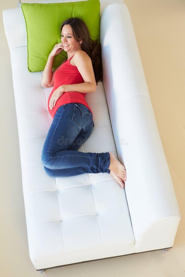 Över huvudet sikt av gravida kvinnan som kopplar av på soffan arkivfoto