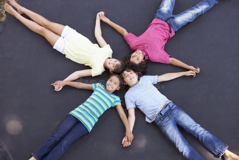 Över huvudet sikt av gruppen av barn som tillsammans ligger på trampolinen royaltyfria foton