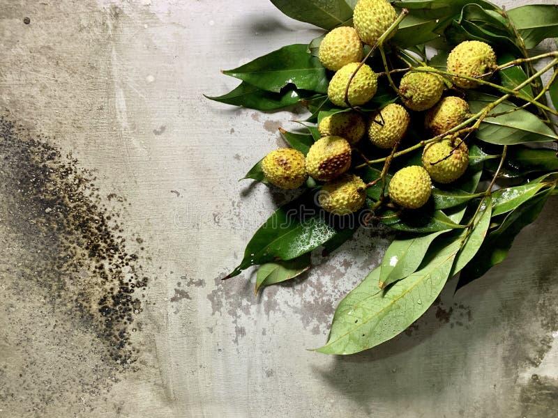 Över huvudet sikt av litchiplommoner med gröna sidor och droppar av vatten på en lantlig bakgrund, matfotografi arkivfoto
