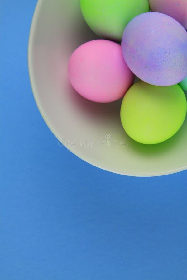 Över huvudet sikt av ljust målade easter ägg i en vit bunke på blå bakgrund arkivbild