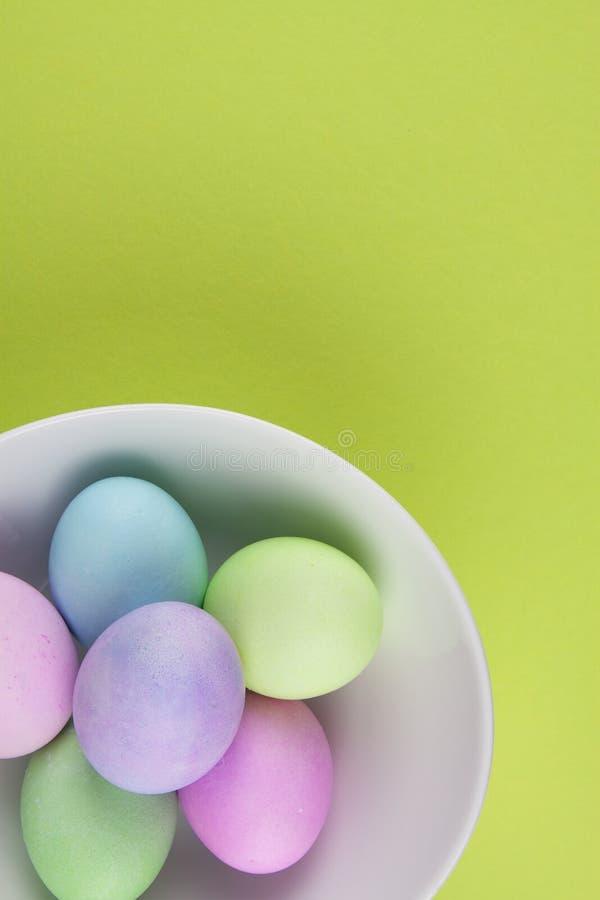 Över huvudet sikt av ljust målade easter ägg i en vit bunke på grön bakgrund arkivbild