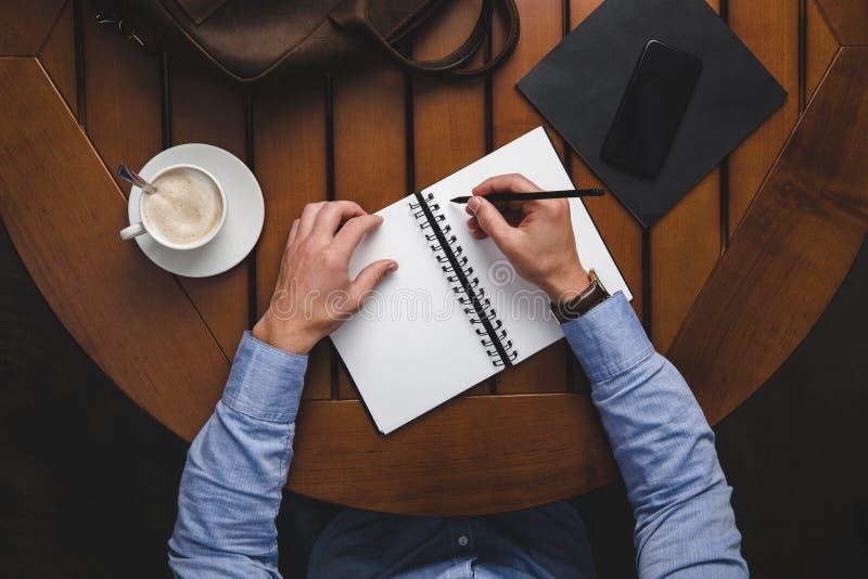 över huvudet sikt av manhandstil i notepad på trätabellen med kaffe royaltyfria foton
