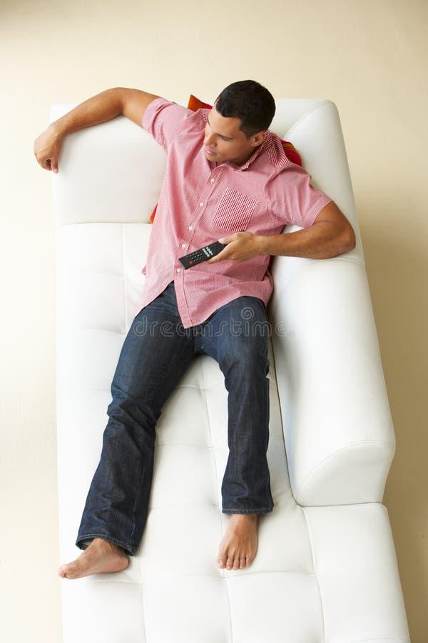 Över huvudet sikt av mannen som kopplar av på soffan arkivbild