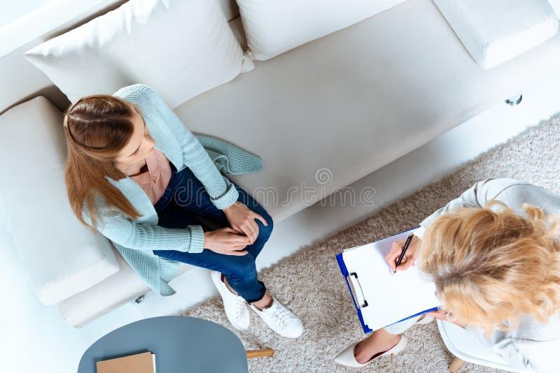 över huvudet sikt av psykoterapeuthandstil på skrivplattan medan ungt tålmodigt sammanträde royaltyfri fotografi